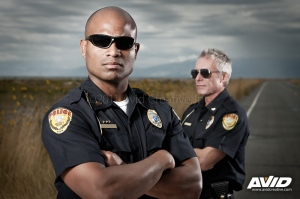 Dramatic portrait of two tough police officers on an empty road with moody clouds and sky. The main officer in front is a younger african american male and his partner in back is an older caucasian man.
