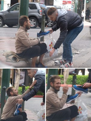 Here's a man giving a pair of shoes to a homeless person.