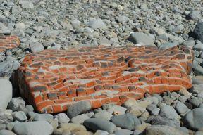 The ocean has worn down this brick wall.