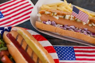 Close-up of hot dog and American flag on wooden table