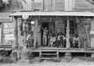 Here are some bros shooting the breeze in 1939 North Carolina. Notice how they didn't even bother to turn those logs into poles. Cool gas pumps too.